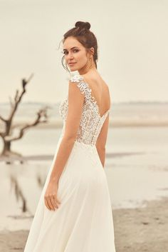 Feel beautiful and comfortable in this light and airy lace illusion bodice A-line gown. It features exposed boning, covered in Venice lace appliqués. A lovely chiffon skirt finishes the look. For additional structure, this style is also available with the bodice lined to the back.