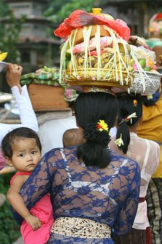 Woman on procession with her daughter in her arms, Bali, Indonesia