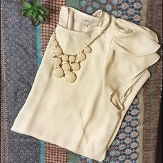 Ann Taylor LOFT blouse NWOT! Sheer ivory button-back short sleeve tee. Dress it up with a blazer, or down with shorts & sandals. Brand new! LOFT Tops Blouses