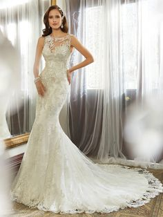 Sophia Tolli   Style No. › Y11557   Detail is key in this gown with a strong focus on eye-popping embellishments. Kea, a slim sheath in misty tulle, features a unique illusion bateau neckline adorned with decadently hand-beaded lace appliqués. A gorgeous keyhole back showcases a major trend for the season. A chapel length train with scalloped hem lace and a back zipper [...]