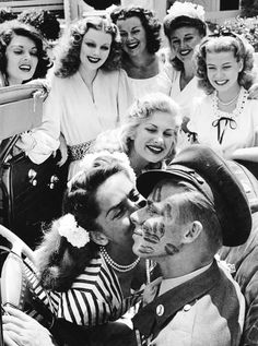 Pvt. John Farnsworth covered in kisses by famous pinups and actresses (L to R : Lynne Baggett , Dolores Moran , Barbara Hale ,Ginger Rogers, Gloria DeHaven , Chilli Williams and Jinx Falkenburg.) 1944 (via)