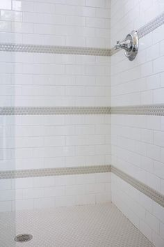 A polished nickel shower kit is mounted to white subway shower surround tiles accented with gray penny tiles. Tile Shower Niche, Tile Walk In Shower, Gray Shower Tile, White Subway Tile Bathroom, Subway Tile Showers, Concrete Bathroom, Neutral Bathroom, Master Shower, Bathroom Showers
