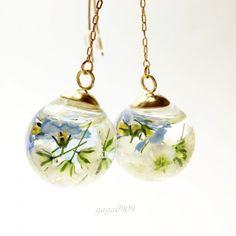 勿忘草とかすみ草のスノードームのフックチェーンピアスになります。 勿忘草とかすみ草をドライフラワーにし、特殊な液体(人体に影響なし)と一緒にガラスドームに閉じ込めました。 ゴールドのダイヤカットガラスも閉じ込めているので、ガラスドームの中で、キラキラ花たちと一緒に動きます。 ガラスドームの上にゴールドのキャップをつけ、シンプルに仕上げました。 ※天然のお花を使用している為、左右の大きさや形が違います。 予めご了承ください。 【サイズ】 ●ドーム部分 約(縦)2.4cm×(横)2cm ●チェーン 約4cm ●ピアス部分 約4.5cm ・本物の花をドライフラワーにし使用しています。 徐々に色が変化してしまいます。 日常でご愛用いただき変化をお楽しみください。 ・作品はとても繊細な作りになっております。 衝撃等がありますと破損の可能性がございます。お取扱いにはご注意ください。