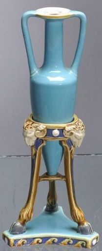 Minton majolica bud vase, England, 1863, amphora vase seated in a tripod stand, stand molded with ram's heads and hoof feet, impressed mark to base, ht. 6 7/8 in.  |  SOLD $1,175
