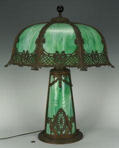"Table Lamp with Slag Glass Shade and Base -  Green slag glass shade, base with metal overlay decoration featuring swags and griffins. 23 3/4"" H x 20"" W. American, early 20th century. Condition: Overall good condition with no apparent chips or cracks to slag glass. Minor loss to metal overlay decoration of base."