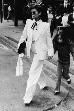 Bianca Jagger wears double-breasted white suit as she & daughter Jade walk across street in London, May 4, 1979
