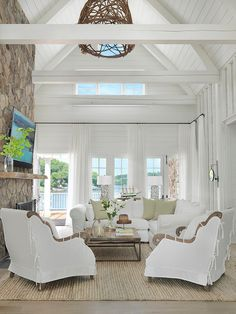 all white greenroom in a beach house, vaulted ceiling, natural stone, white draperies