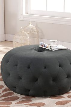 Tie your room together with this well-designed modern ottoman. This large, circular footstool softens any home space with its lack of angles and its versatile linen upholstery that features surplus of button tufting. Bring an element of traditional style to your home with this plush piece.