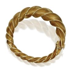 18 KARAT GOLD TWIST BANGLE-BRACELET, SCHLUMBERGER FOR TIFFANY & CO. The hinged bangle of twist design, gross weight approximately 46 dwts., internal circumference 6 inches, signed Schlumberger, Tiffany & Co.