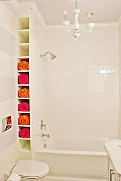 Shelf for towels, on the wall, by the tub. Small bathroom organization. I think it would be cool to paint the inside of the shelf lime green with pink towels.