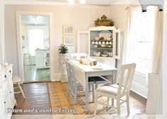 Creating Cozy Country Style on a Budget An old dining table is painted white and gray. The end chairs were church sale finds and were painted and reupholstered with budget-friendly drop cloth.