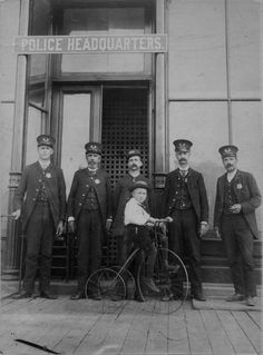 Photo of entire Lansing, MI police force ca. 1890. Photo taken in front of Police Headquarters located at 204 E. Michigan Ave. From left: George Kohler, John N. Bush, Ed Bates, Chief Ben Harrington, father of Ben Harrington, Jr. (on tricycle), Photo by John Collins.