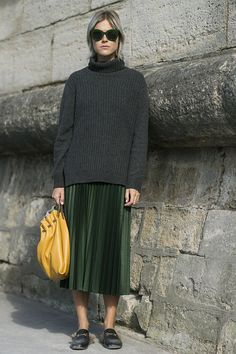 A turtleneck sweater, pleated skirt, and brightly colored bag