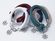 This bracelet has a crochet cotton cord, that makes a knot around the silver metal ring, in which there is a dangling silver plated metal rudder