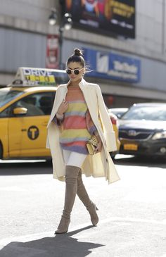 Camila Coelho on her way to Herve Leger show in NYFW wearing a colorful knit sweater, a beautiful cream coat, white pants, grey over-the-knee boots and a light yellow mini purse.  A caminho para o show de Herve Leger usando um suéter de lã colorido com um casacão claro nos ombros, calça branca, bota over the knee cinza, e uma mini bag.