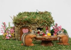 Miniature chipmunks enjoy a little picnic in front of a fairy house in the mini fairy garden.