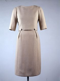 Beige wool crepe dress with overblouse, by Oleg Cassini, American, 1961. Worn by Jacqueline Kennedy to Inaugural ceremonies, Washington, DC, January 20, 1961. For the luncheon at the Old Supreme Court Chamber that followed the swearing-in, the new First Lady revealed a slender variant of the overblouse dress designed by Cassini as a counterpoint to the A-line volume of the inaugural coat.