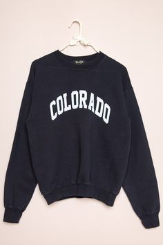 Soft fleece-lined sweatshirt in navy with COLORADO graphic printed in white with textured paint flocking. College Shirts, College Sweatshirts, Lounge Outfit, Lounge Clothes, Comfy Clothes, Vintage Nike Sweatshirt, Weird Fashion, Hoodie Outfit, Brandy Melville