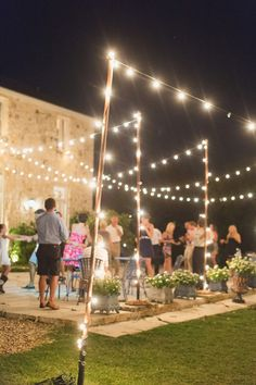 Nighttime outdoor small wedding reception. Like the simple string lights.