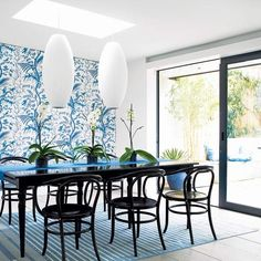 For this decorating idea, use a bold botanical wallpaper to create a feature wall in a smart dining area. Dark furniture makes a striking contrast with the trailing leaf design, while the shape of the scrolling bentwood chairs complements it.