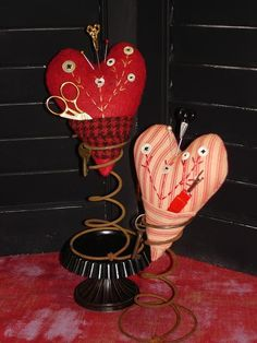 Love how these cute heart pincushions are displayed... on springs!