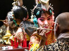 Stock Photo : Chinese opera singer applying makeup to male