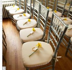 Even Jessika and Michael's seating is celeb-worthy. The icy chiavari chairs feature steel metal frames and clear Lucite details, which reflect the candlelit glow and rich colors present in the room. A single daffodil is placed on each seat, which Jes...