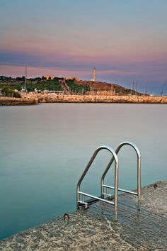 Italy, Apulia, Lecce district, Salentine Peninsula, Salento, Santa Maria di Leuca, View of the town's headland with the sanctuary and the lighthouse as seen from the harbour area