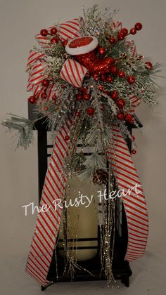 Our lantern swags are great way dress up any lantern! This swag is decorated with red, white and silver striped ribbon, various snowy greens,