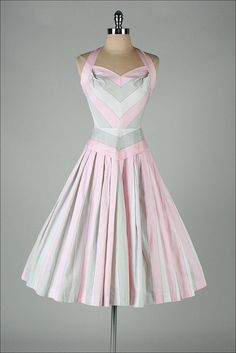 Figure-flattering 1950s pink and grey halter dress with flared skirt. So cute!