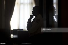 The silhouette of a Federal Reserve police officer is seen standing in an…