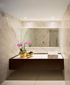 In this bathroom, stone covers the walls and a back-lit mirror creates soft ambient lighting. - flowers and gold pot