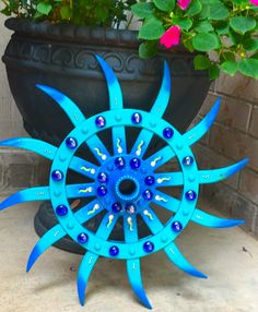 Metal garden flower made from vintage rotary hoe tiller wheel.