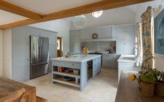A large kitchen island in a Shaker kitchen featuring shelves and a wine cooler.