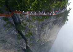 The Coiling Dragon path is in Zhangjiajie National Forest Park in Hunan province, and a new section opened to tourists on Monday. - People walk around a glass walkway in Tianmen Mountain in Zhangjiajie National Forest Park, Hunan, China (1 August 2016)