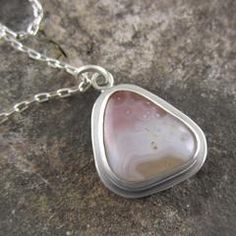 We love this unique Lake Superior agate pendant with the slight purple ombre coloring and smattering of white specks. Reminds us of a twilight evening!
