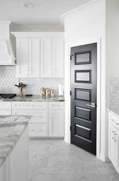 White shaker cabinet kitchen with lucite acrylic handles and a black pantry door.