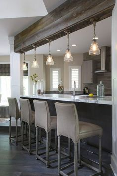 Beautiful kitchen features stacked rustic wood ceiling beams accented with five glass light pendants illuminating a gray and white marble top kitchen island fitted with a stainless steel sink and gooseneck faucet lined with taupe leather barstools.