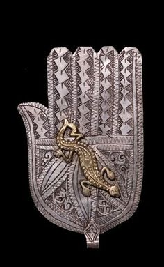 Lovely Hamsa, with gorgeous line work and an excellent bronze lizard crawling across the palm. No info on this.