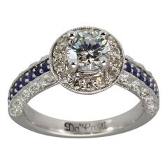 Antique Round Engagement Setting With Blue Sapphires -   This ring is designed to hold between a 0.50ct and 0.90ct ROUND center diamond.      This ring has blue sapphires and brilliant round diamonds which enhance the center diamond. There are engravings on the sides, milgrain on the shank and scroll work near the top which gives it the unmistakable appearance of an antique ring. Our rings have thick and durable shanks which will give many years of trouble-free wear.   We use only...