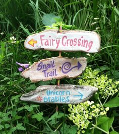 garden fairy sign post with 3 signs, rustic painted signs, snail trail, fairy crossing, unicorn stables on a signpost