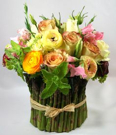 arrangement with spring colored Roses, Sweet Pea, Spray Roses, Mint Leaf, lined with Asparagus