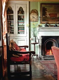 Warm tones of an oak settle, a lace maker's antique lamp stand by the fire and bare floor boards with a rich, vintage carpet ~ This cottage has been carefully preserved and enhanced with beautiful period finds.