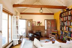 Erin & Nathan's Collaboratively Creative Bungalow- exposed beams orange beautiful open living room