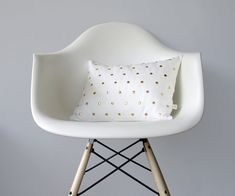 A cream linen pillow cover dotted with shiny brass studs.