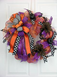 Dotted ribbons, gerber daisies and mini black pumpkins are fun accents on this simple Halloween design. A deco mesh wreath filled with loops of dotted black/white ribbon and sparkly purple ribbon. A g