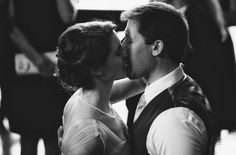 Black and white photo of a bride and groom's first kiss at their wedding ceremony.