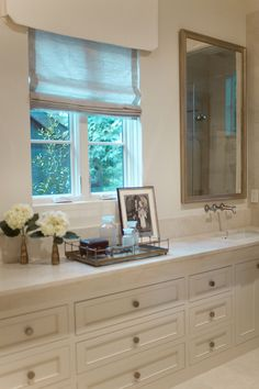 Traditional master bath features long wall-to-wall dresser style vanity topped with white marble framing off set sink paired with wall-mounted faucet and beveled mirror situated next to window dressed in white valance and gray linen roman shade.