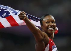 Carmelita Jeter holds the American flag as she celebrates winning silver in the women's 100m final