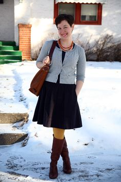 I like the cropped cardi, full skirt, red necklace, mustard tights combo, and the boots.  Cute.